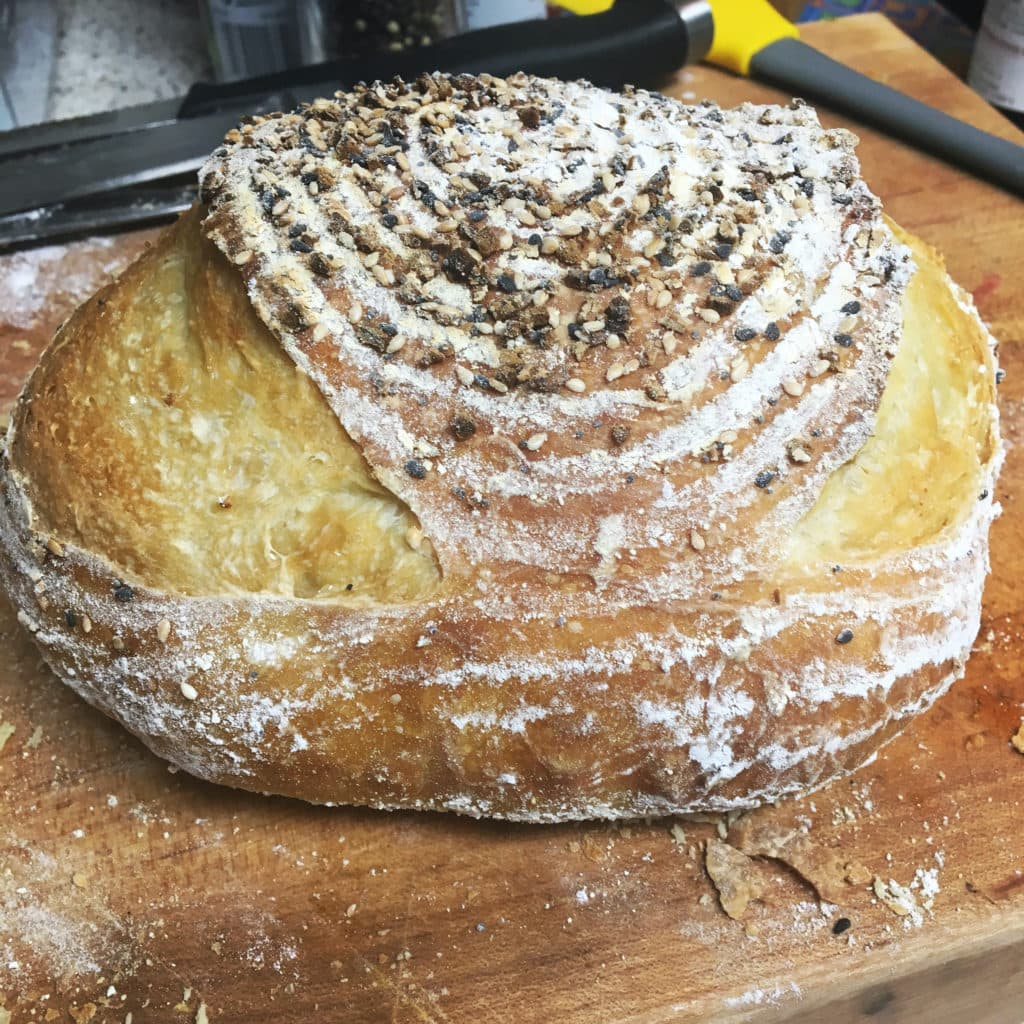 a loaf of bread with two slashes on either side and a coil pattern in flour on the crust