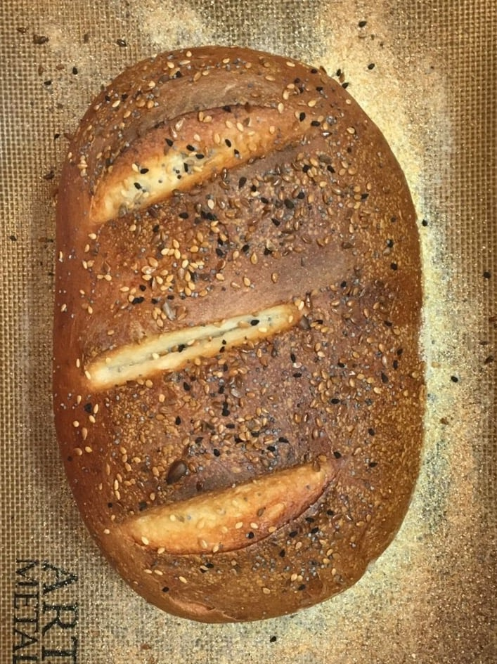 a dark brown oval loaf of bread with three slashes cut across the top