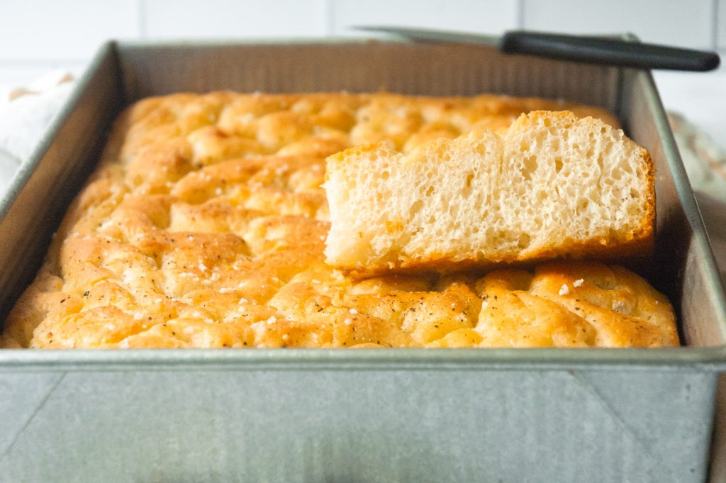 a sheet pan of focaccia bread. a square has been cut out of the middle and is propped up showing the airy, bubbly interior of the bread.