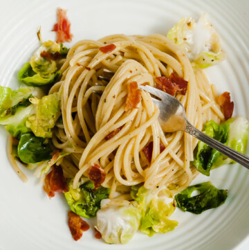 an overhead shot of brussels sprouts carbonara in a white bowl. a fork sticks out of the noodles, resting onn the lower right edge of the bowl.