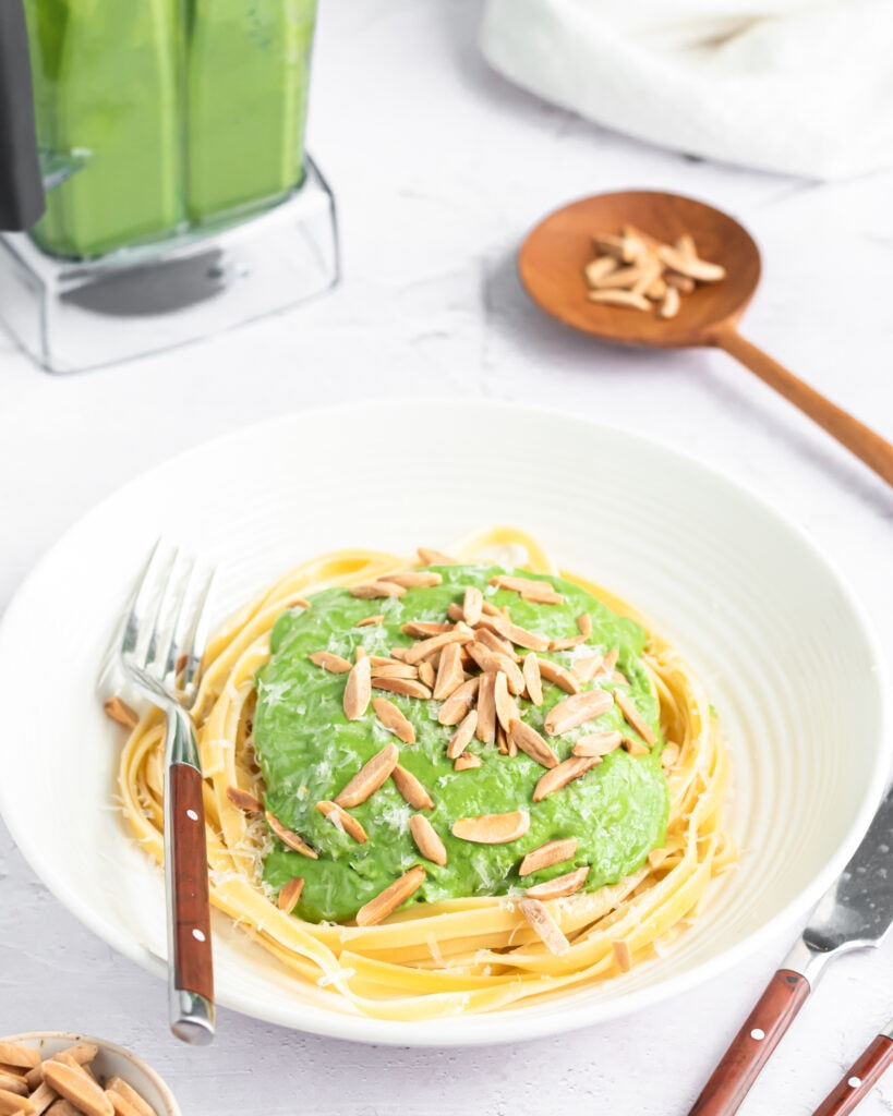 a bowl of green spaghetti sauce poured overtop bare noodles and topped with parmesan cheese and almond slivers