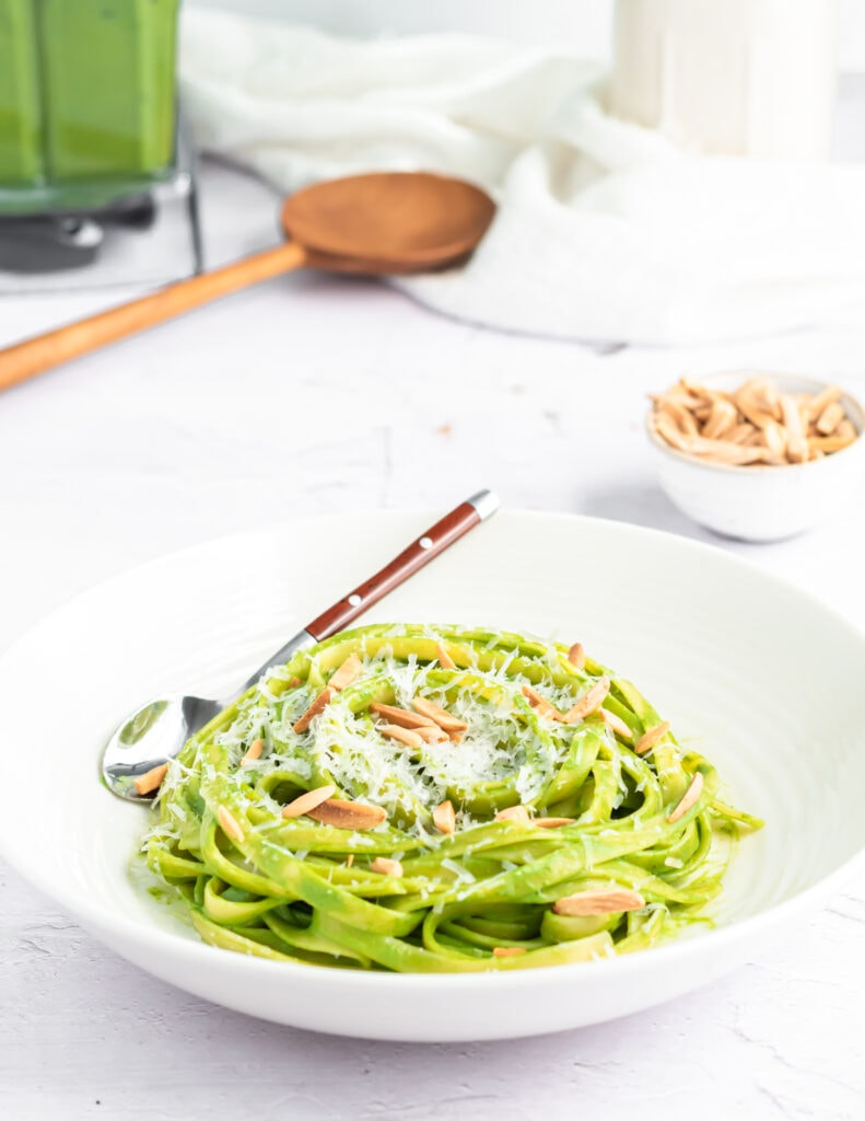 a close up of fettuccini pasta coated in green spaghetti sauce in a shallow white bowl. it is topped with parmesan cheese and toasted almond slivers.