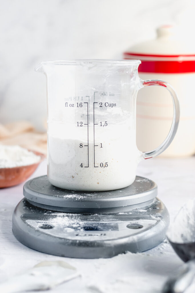 a 2 cup glass measuring cup sits on a silver kitchen scale. the sourdough starter in the cup comes up to the 1 cup line.
