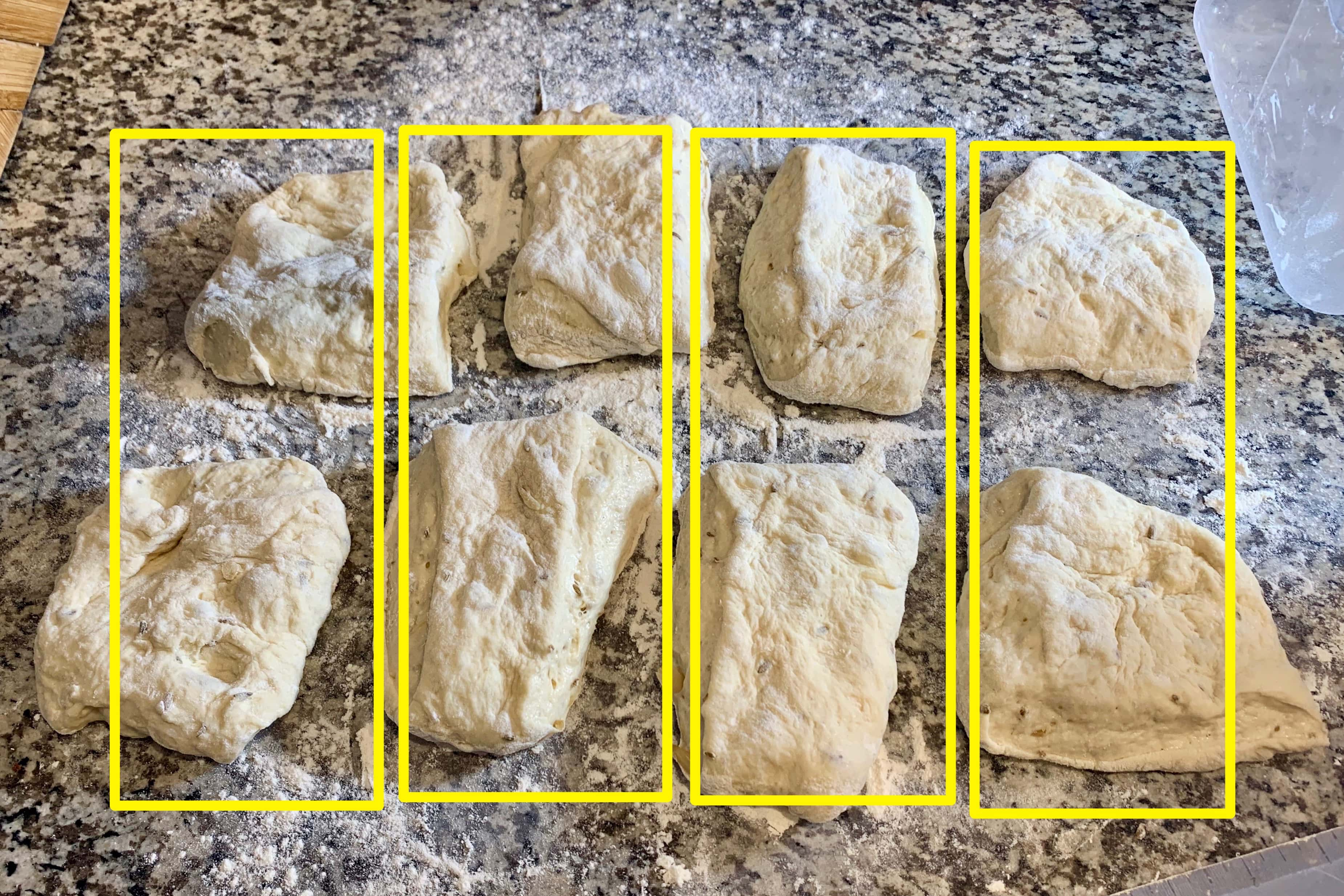 the flattened ciabatta dough cut into 8 equal pieces lies on the counter. overtop the image has been drawn four large, vertical yellow rectangles showing that you can cut the dough into four equal pieces instead.