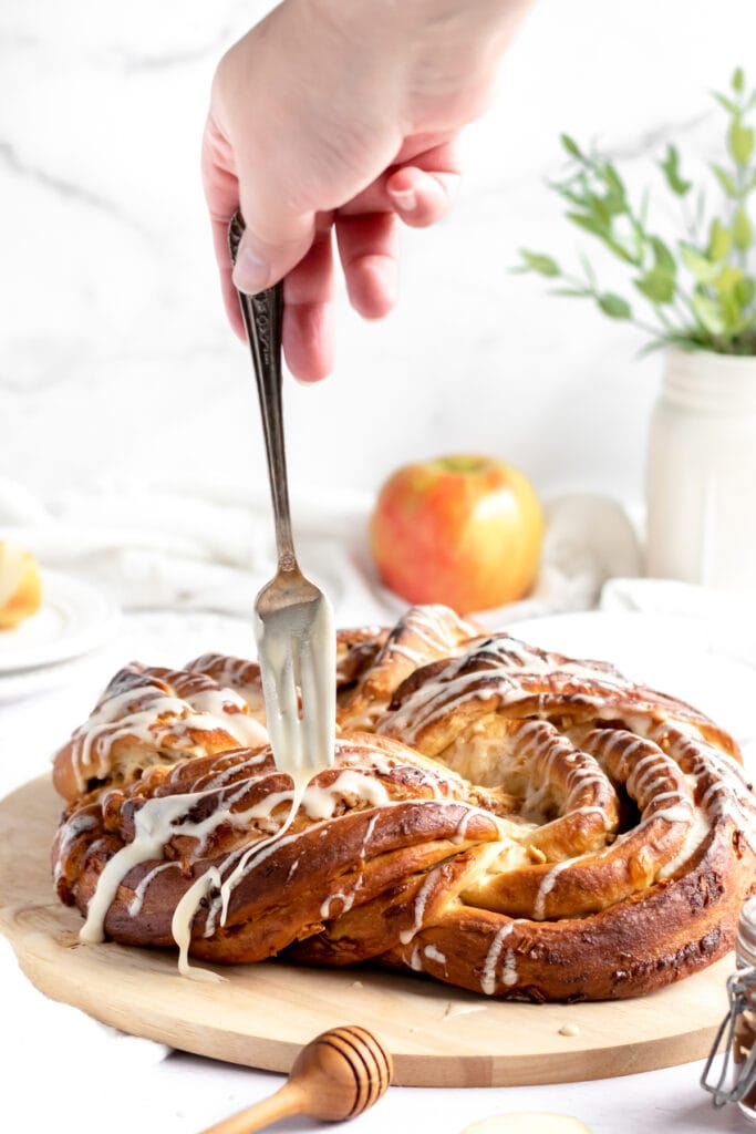 The baked apples and honey babka sits on a cooling rack on a wooden cutting board. It's pretty bare, but golden brown with dark brown apple butter around the apple pieces and in all the creases.