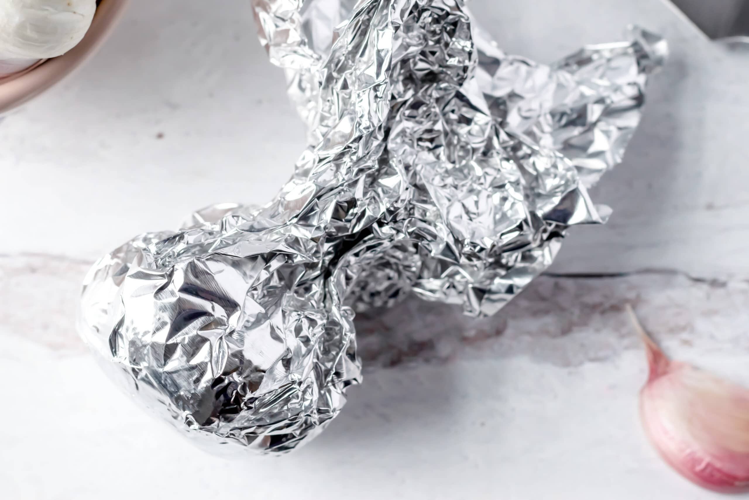 a crumpled aluminum foil packet with has a garlic bulb in the bottom ready to be roasted