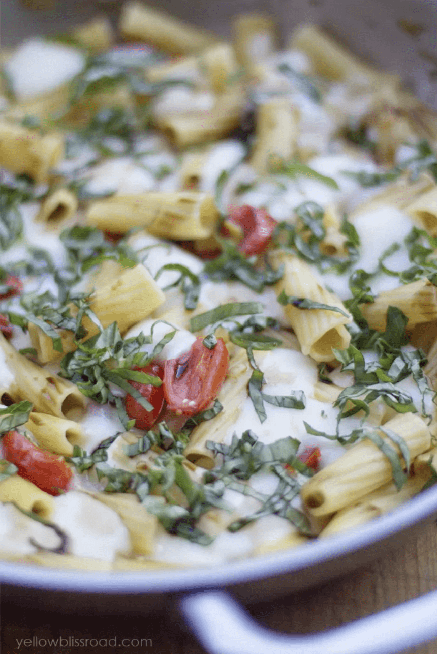 """A close up of one-skillet dinner """"One-Pan Caprese Pasta"""" in a silver pan with side-handles. In the pot is cooked rigatoni noodles, halved and wilted cherry tomatoes, thinly sliced basil, and large pools of melty mozzarella cheese."""