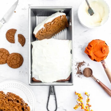 pumpkin gingerbread cake in a loaf pan with cream cheese frosting