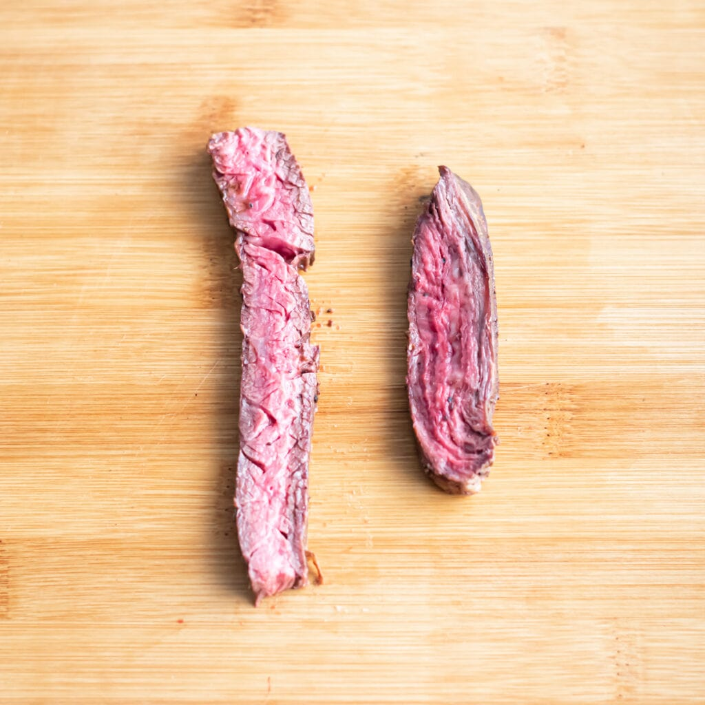 two slices of meat, one cut against the grain and one cut with the grain