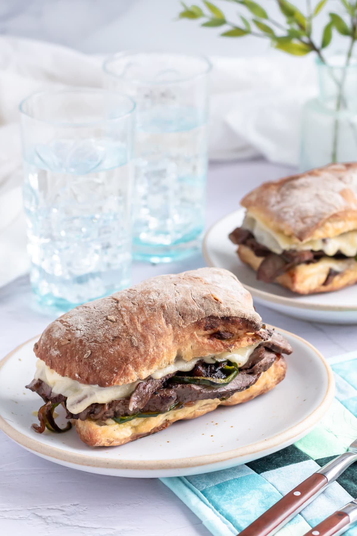 two halves of a cheesesteak sandwich on a small plate on top of two napkins. another cheesesteak sandwich sits on a plate behind it along with some glasses of water and a newspaper.