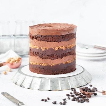 a mocha hazelnut layer cake on an overturned metal fluted plate