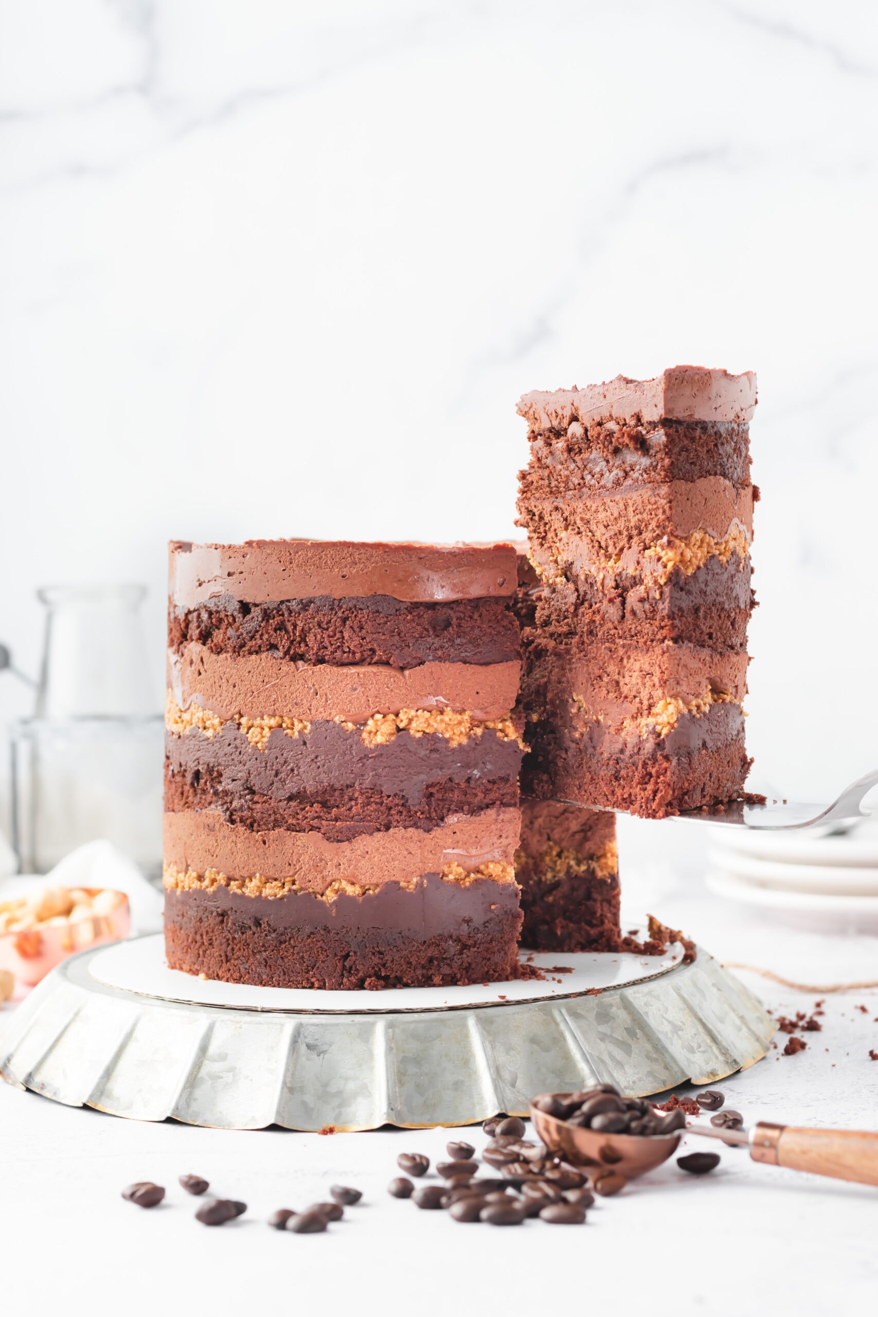 a large slice of cake being lifted out of a mocha hazelnut layer cake