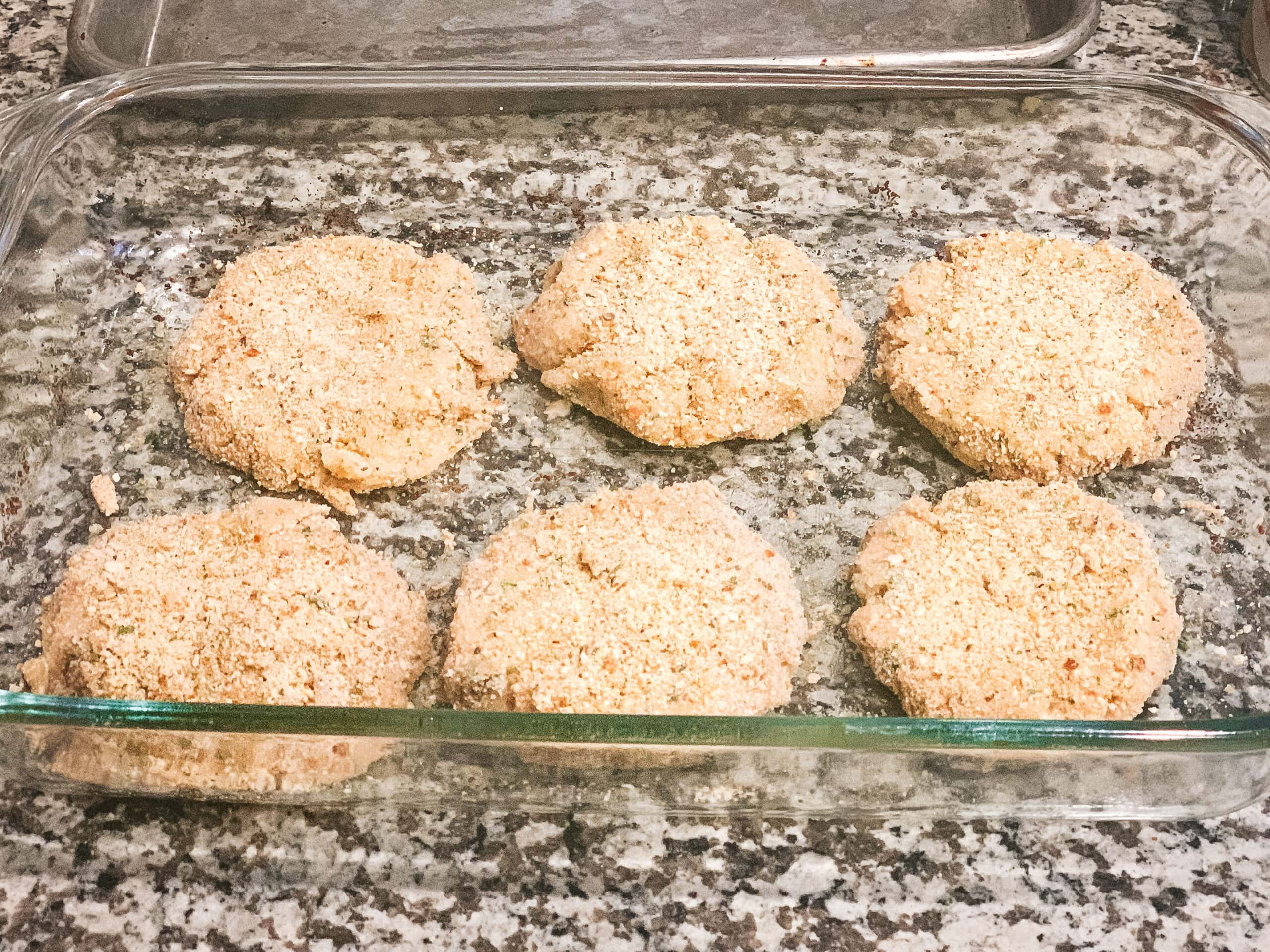 6 tuna cakes sit in a clear glass casserole dish before going in the oven. They are coated in bread crumbs.
