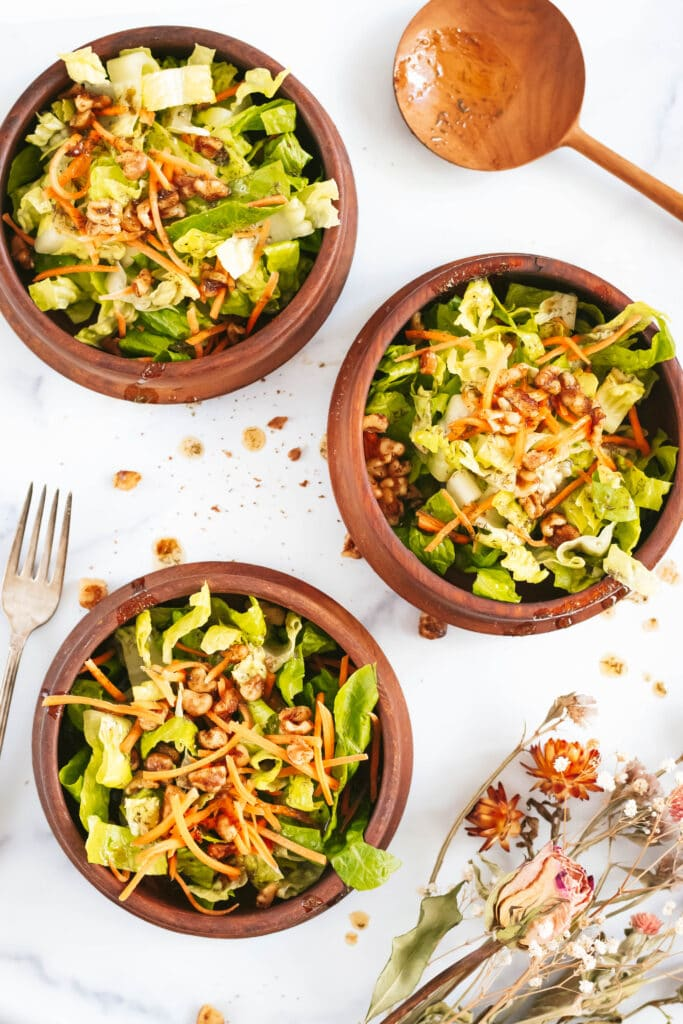 an overhead shot of three wooden salad bowls filled with lettuce and walnut salad. a wooden spoon is at the top right of the photo, a fork on the middle left side, and a bouquet of dried flowers is in the bottom left corner.