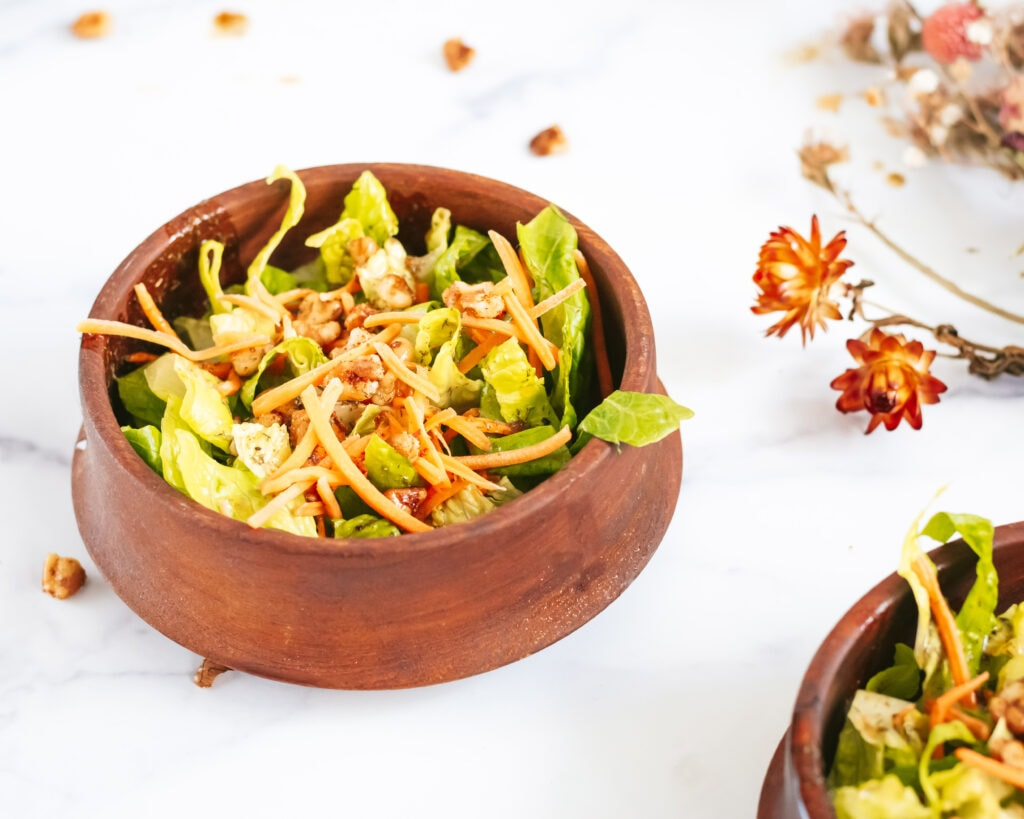 a wooden salad bowl with lettuce and walnut salad in it. topped with crunchy carrots and toasted walnuts. to the right is a bouquet of dried flowers.