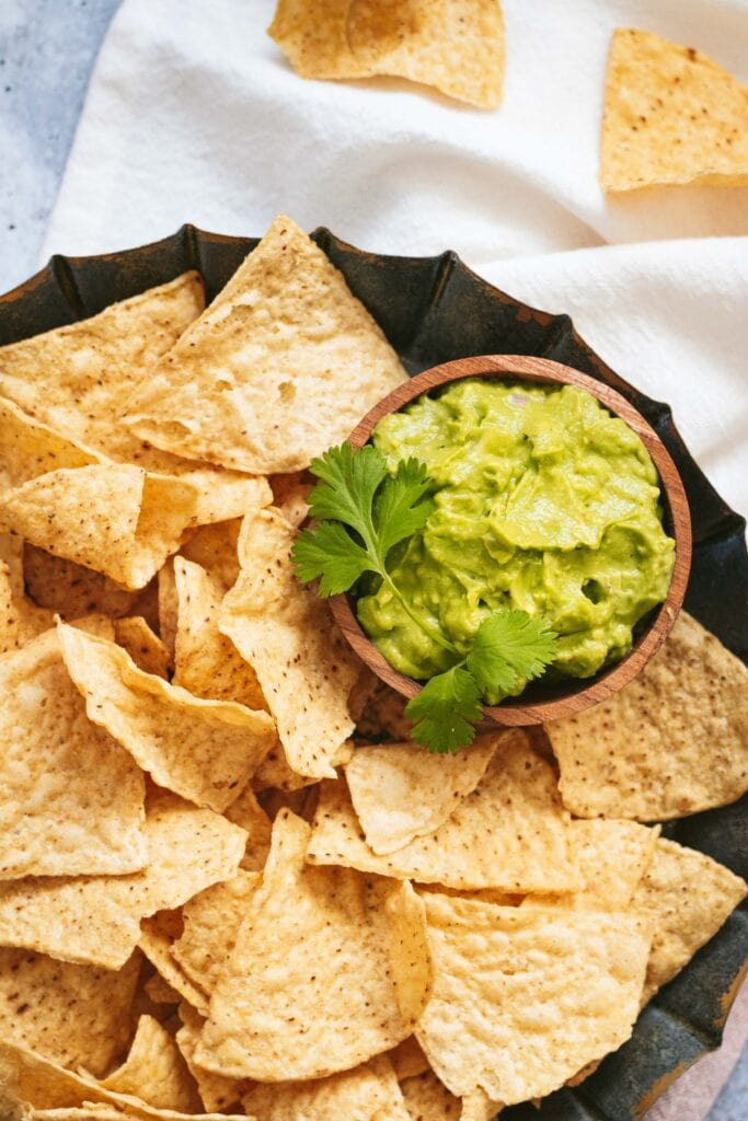 an overhead shot of a small wooden bowl of guacamole garnished with a cilantro leaf sits in a bowl of tortilla chips