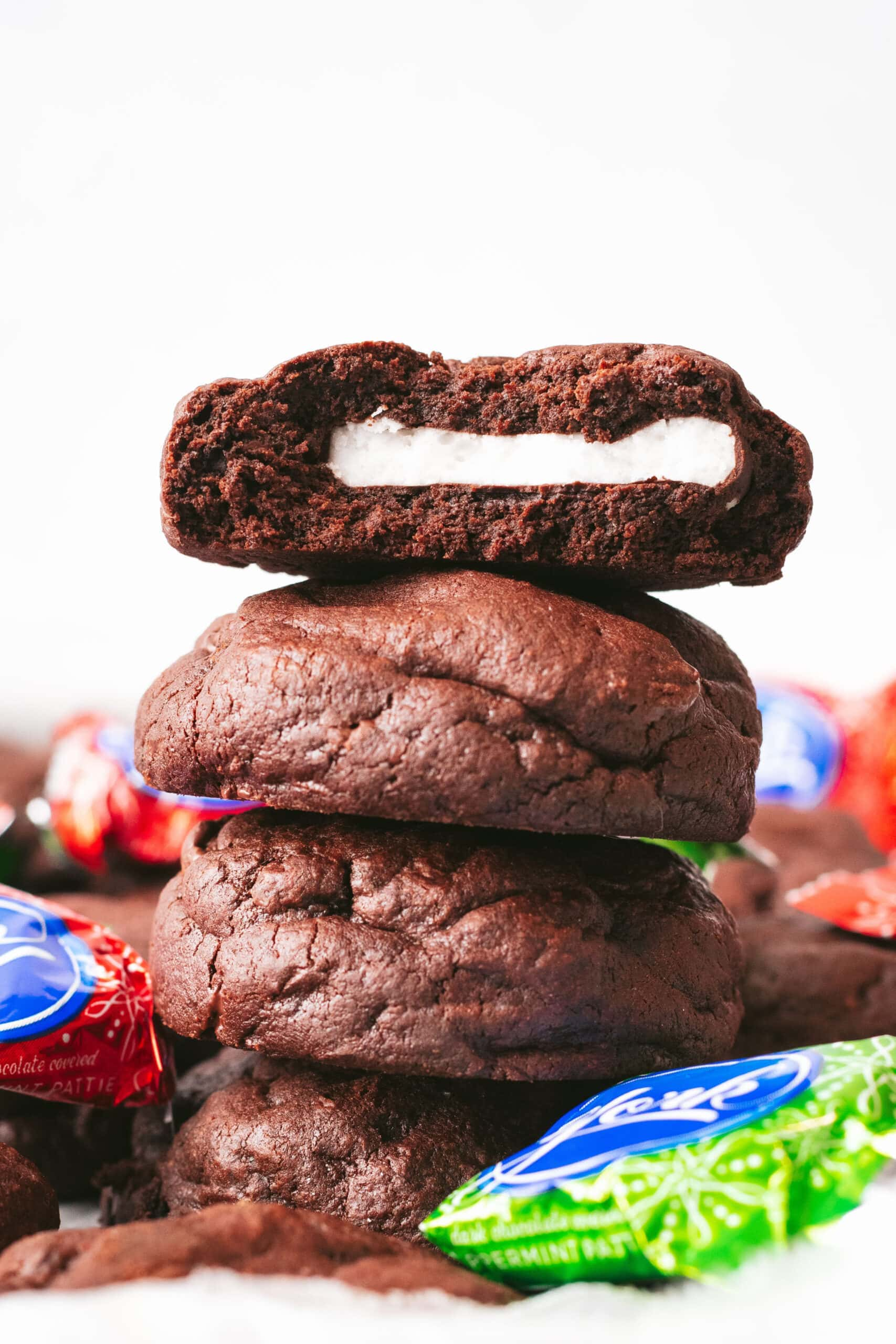 A stack of peppermint patty stuffed brownie cookies. the top one has been broken in half revealing a strip of white peppermint filling inside.