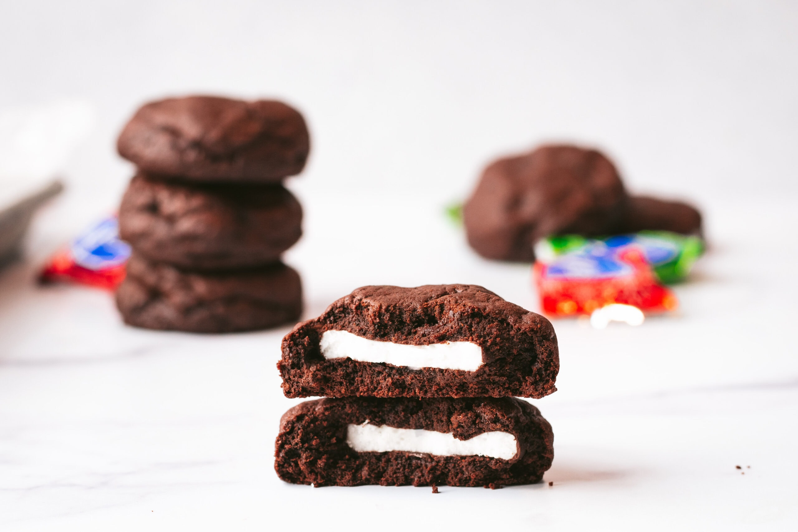 a close up of a cookie broken in half and stacked on top of itself, revealing the mint center.