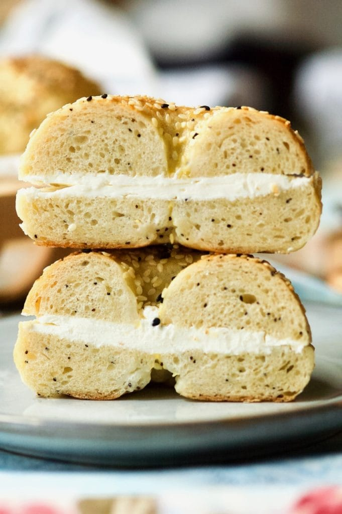 a bagel with cream cheese sliced in half, one half stacked on top of the other facing the camera