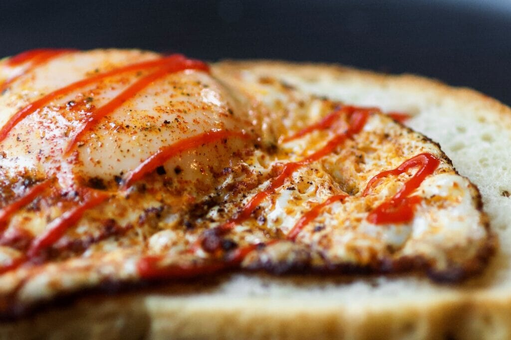 an extreme close up of a paprika fried egg on a piece of toast with hot sauce