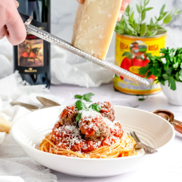 grating parmesan over a bowl of spaghetti