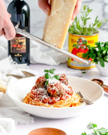 a large white serving bowl filled with spaghetti and meatballs topped with fresh basil and grated parmesan cheese