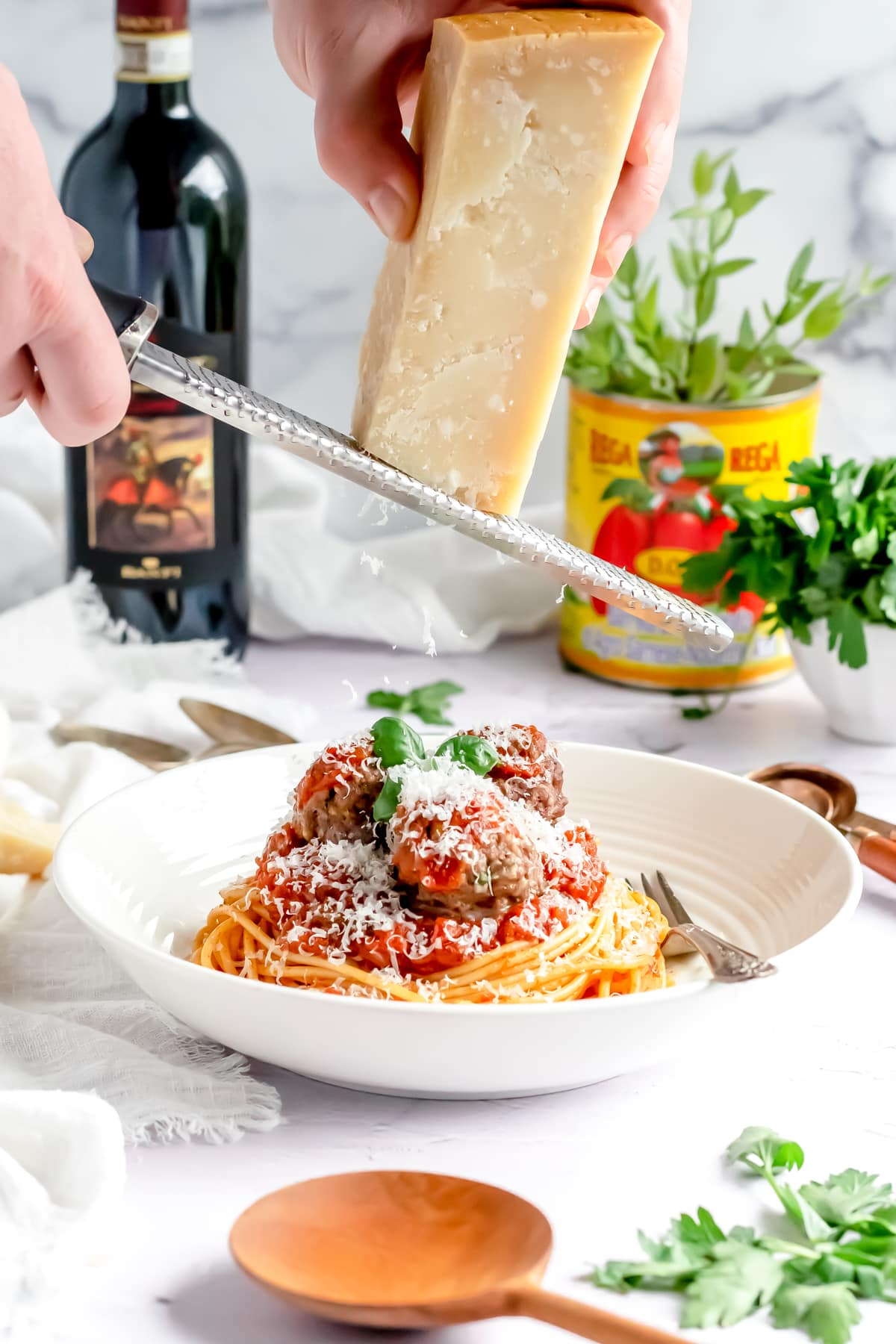 grating parmesan cheese over spaghetti and meatballs