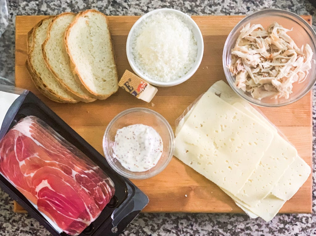 A large wooden cutting board with slices of bread, shredded cheese, shredded chicken, slices of havarti cheese, proscuitto, and a mayo and mustard mixture ready to be turned into grilled cheese chicken cordon bleu.