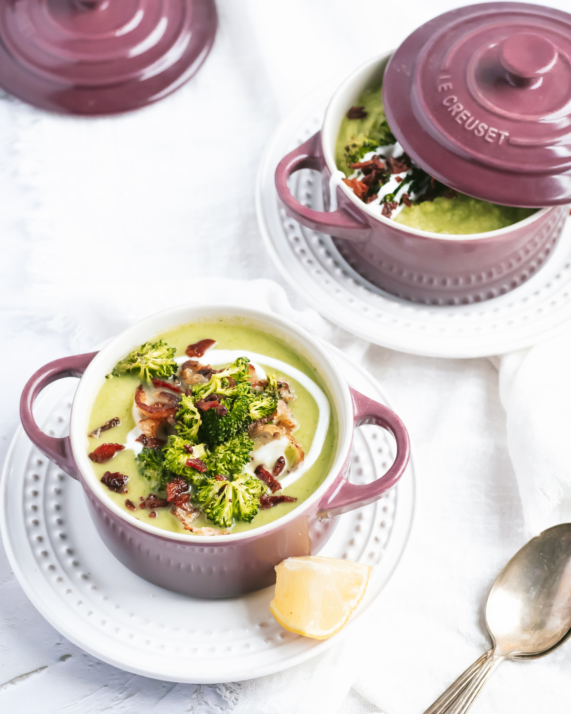 Two ramekins of broccoli stalk soup with all the fixins. A spoon rests on the table next to them.