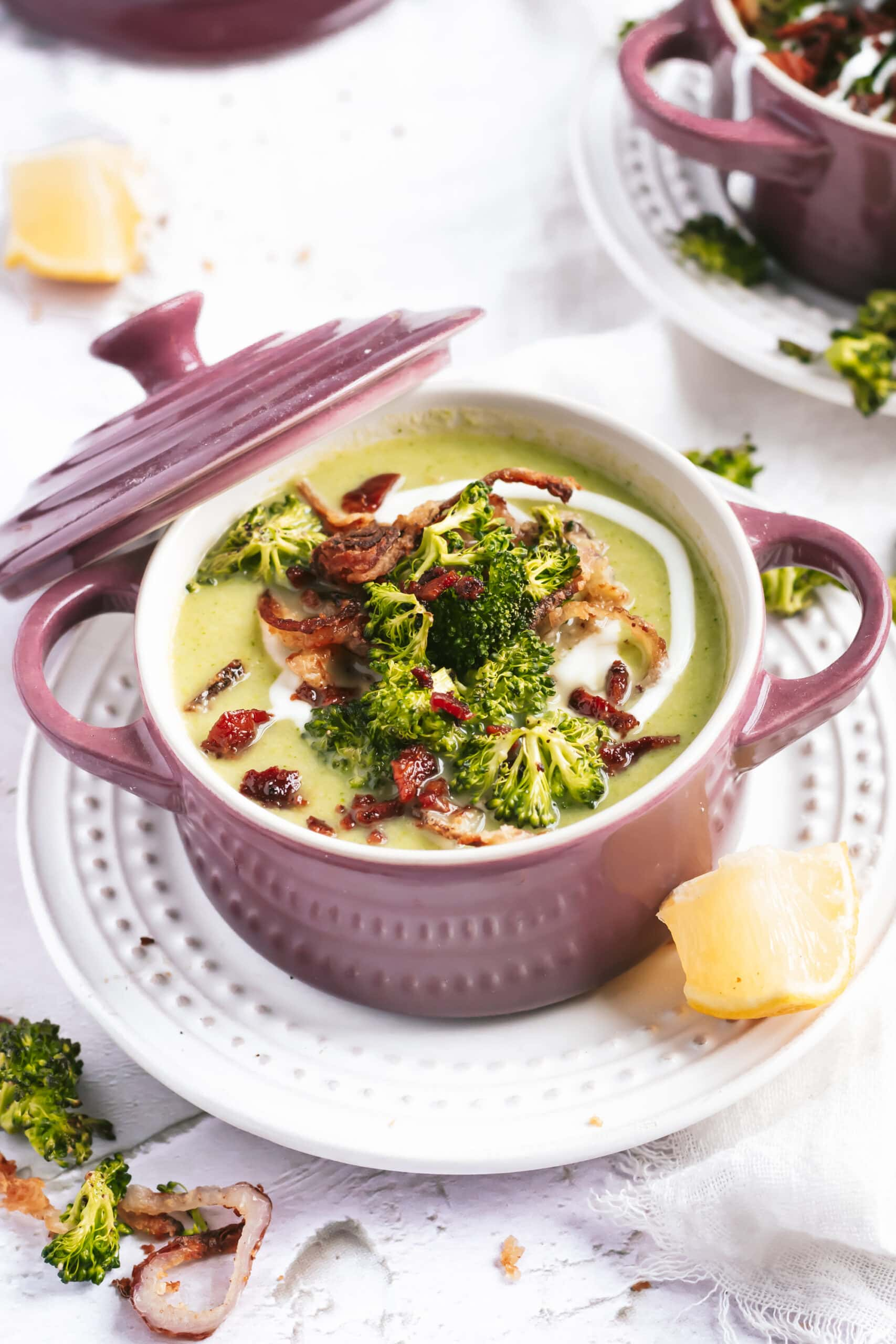 An overhead shot of broccoli stalk soup in a ramekin, with all the toppings.