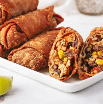 an overhead shot of four egg rolls sliced on a diagonal lined up next to each other on a small grey plate with two lime wedges. next to the plate is half a lime and a small bowl of dipping sauce.