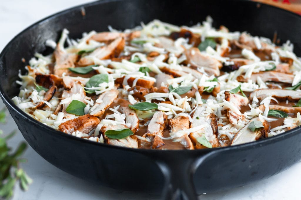 a chicken marsala pizza before going in the oven sitting in a cast iron pan and topped with shredded cheese, pieces of chicken, and fresh oregano.