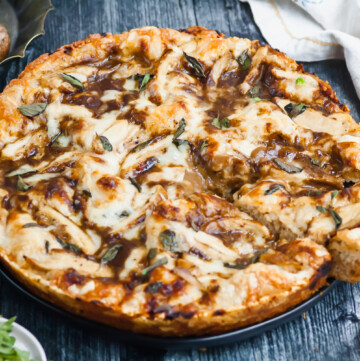 a chicken marsala pizza on a wooden counter. one slice has been cut out of the pizza and pulled back slightly from the rest of the pie.