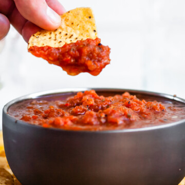 a hand holding a chip which was been dipped in salsa just above a bowl of salsa and plate of chips