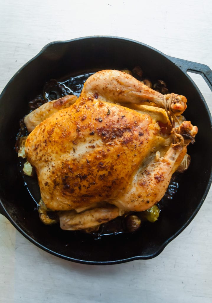 an overhead shot of a roast chicken on a bed of schmaltzy brussels sprouts in a cast iron pan
