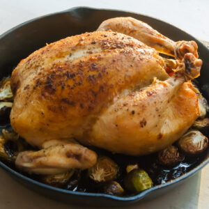 a whole roast chicken sits on a bed of brussels sprouts in a cast iron pan on a metal counter