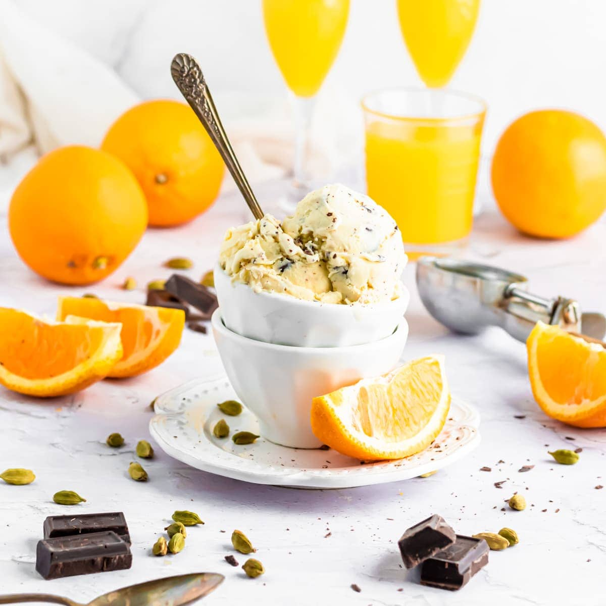 Two scoops of orange-cardamom ice cream with chocolate chips and a hot fudge swirl sit in a ceramic ramekin on a marble countertop. There are cardamom pods scattered across the table and two orange quarters next to it.