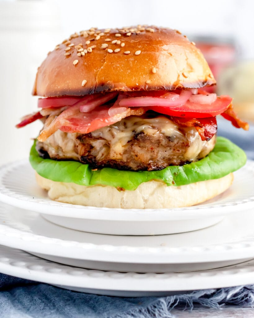 a turkey burger on a bun in the middle of a small plate