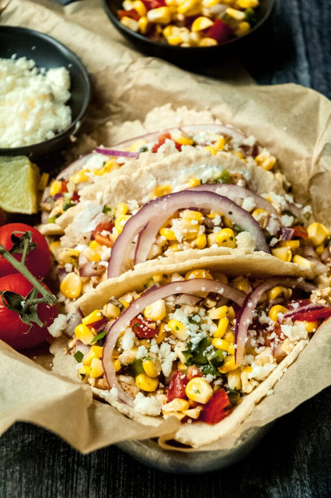 three corn tacos in a sheet pan lined with parchment paper. they're topped with slices of red onion. a small bowl of corn salsa is visible behind the sheet pan.