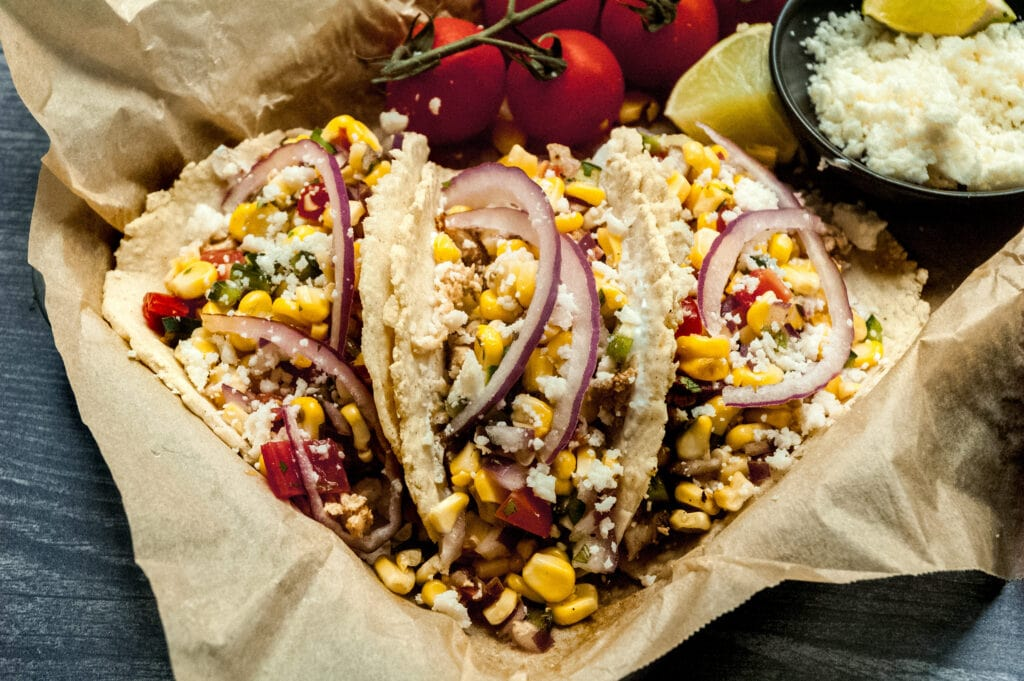 a close up of 3 tacos in a parchment lined sheet pan with a small bowl of cotija cheese, some lime wedges, and whole cherry tomatoes