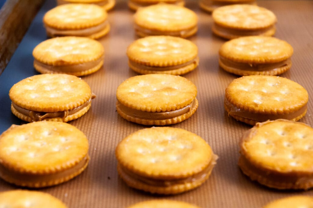 rows of peanut butter and cracker sandwiches arranged on a silicone mat-lined sheet pan
