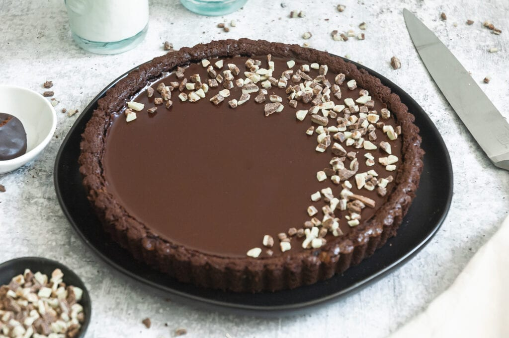 A whole mint chocolate tart sits on a counter. The surface is decorated with andes mint chips in a crescent shape. A small bowl of mint chips is visible in the bottom corner of the photo. A long knife sits to the right of the tart, and the bottom of a glass of milk is visible behind the tart.