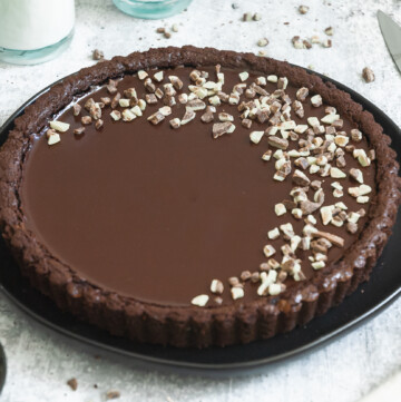 a 45 degree angle shot of a chocolate mint tart decorated with a mint chocolate morsels in a half-moon crescent shape.