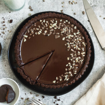an overhead shot of a double mint chocolate ganache tart topped with andes mint chips. a slice has been cut out of the tart. three cookies and a bowl of andes chips sit to the left of the tart. a knife and napkin are to the right. a glass of milk is visible above the tart.
