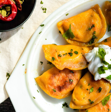 an overhead shot of an oval platter of tikka masala pierogis topped with a dollop of greek yogurt sauce and garnished with cilantro. a small bowl with two red chilies and cardamom pods sits to the left.