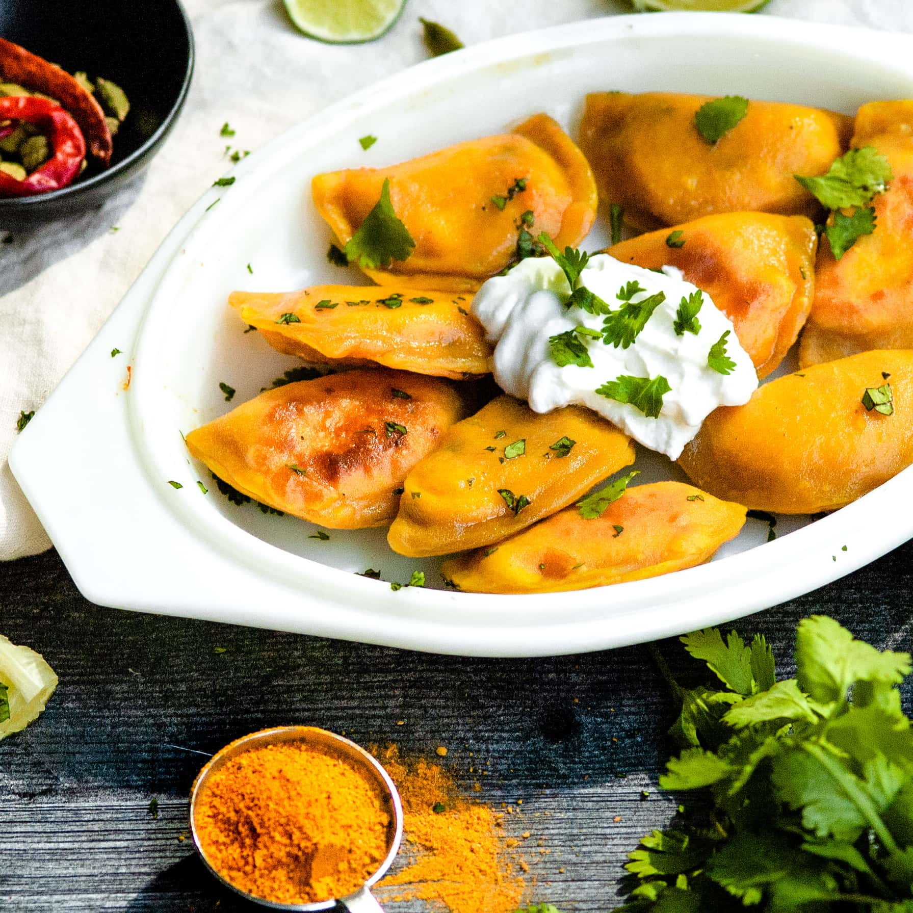 a close cropped shot of an oval platter with tikka masala pierogis on it. a dollop of greek yogurt sits on top of the platter, which is garnished with cilantro. a small measuring spoon with a tikka masala spice blend is on the counter in front of the platter, as is a bunch of cilantro.