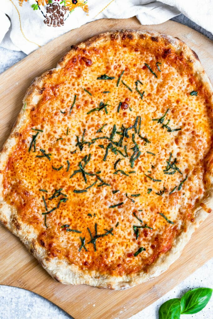 an overhead shot of a cheese pizza topped with chiffonade basil