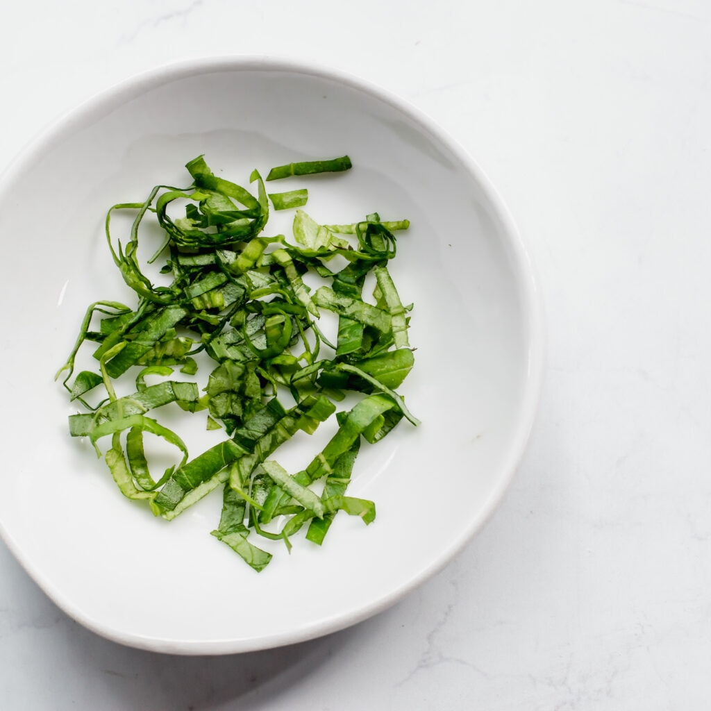 an overhead shot of thinly sliced strips of basil in a small white bowl