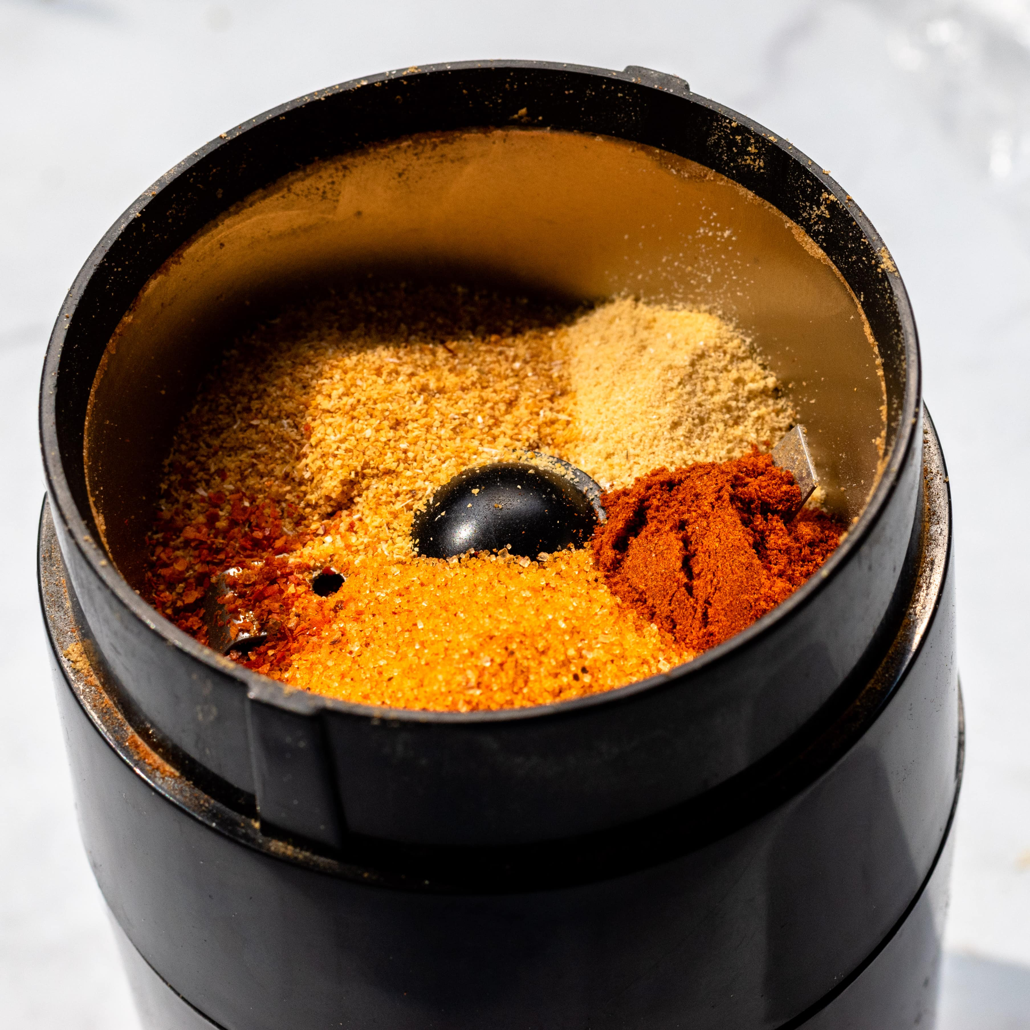 a close up of the seasoned salt, garlic powder, onion powder, paprika, and chili powder in a coffee grinder before grinding them