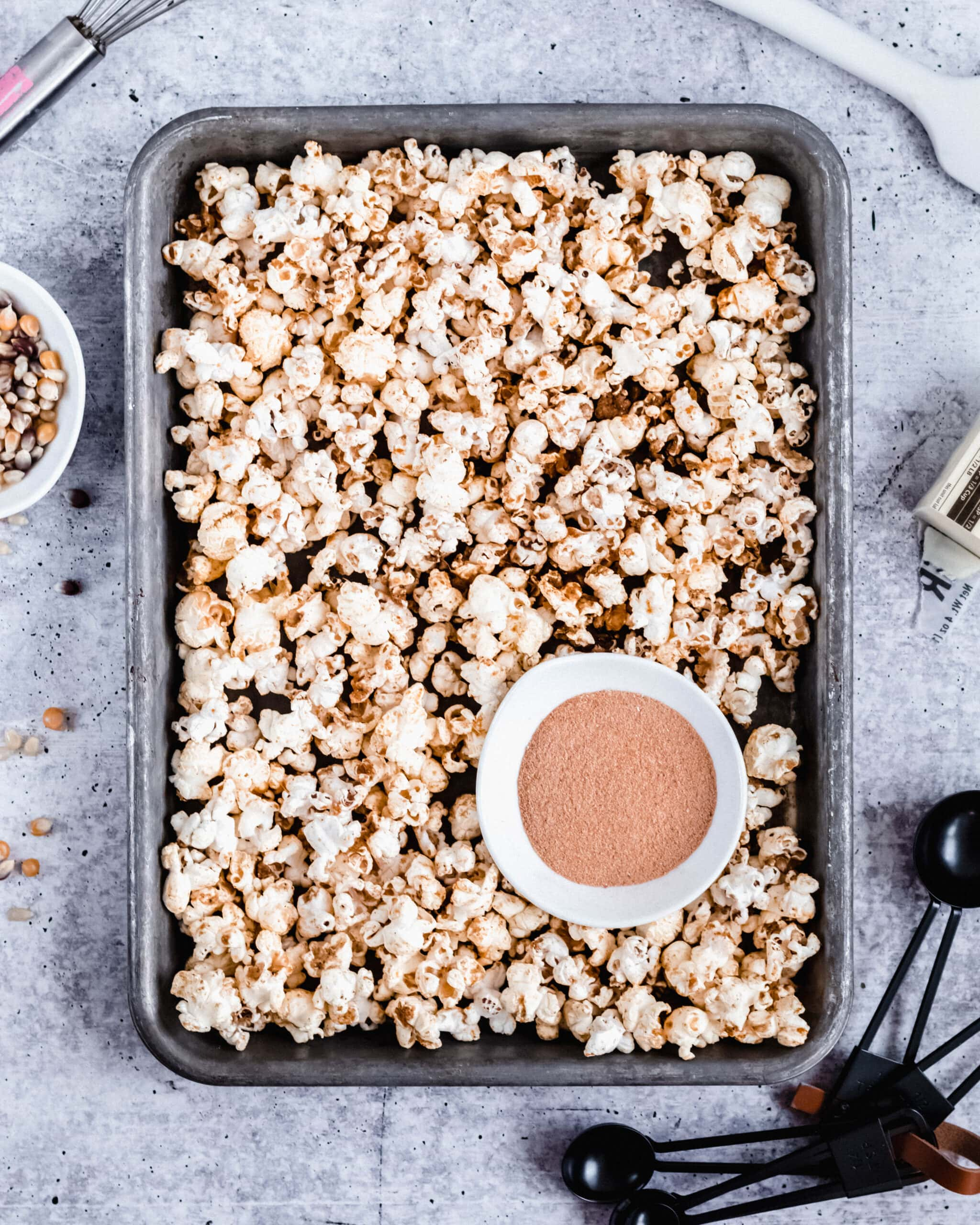 an overhead shot of a sheet pan filled with chex mix popcorn. a small bowl of seasoning mix rests on top of it. a small bowl of unpopped kernels is next to the sheet pan on the left.